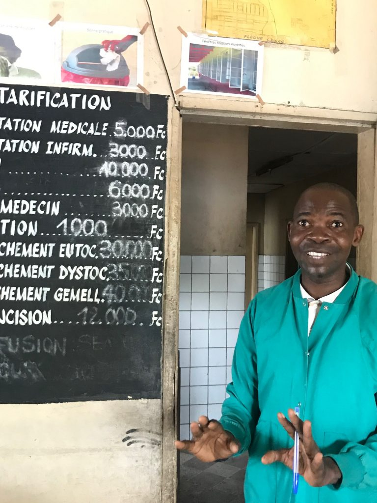 Sjukvårdaren Alain står framför en upphängd griffeltavla som visar hälsocentralens prislista. I dörröppningen bakom honom syns kaklade väggar.