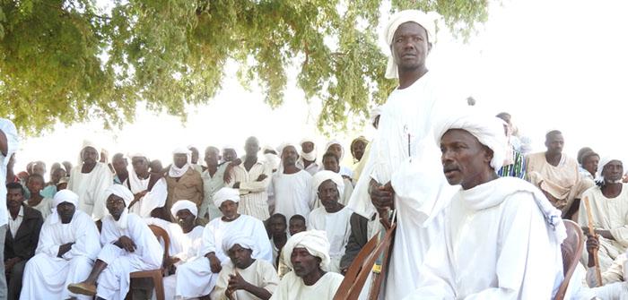Ett femtiotal vitklädda män sitter eller står tillsammans