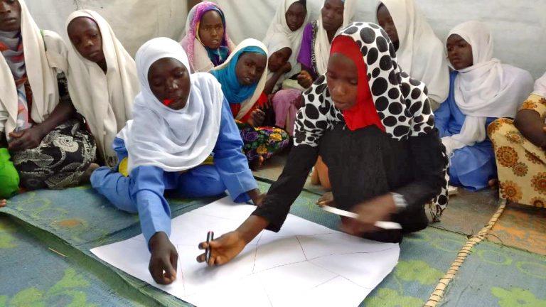 Tolv flickor sitter på golvet. Två av dem sitter i förgrunden och ritar på ett papper medan resten sitter i bakgrunden och tittar på.