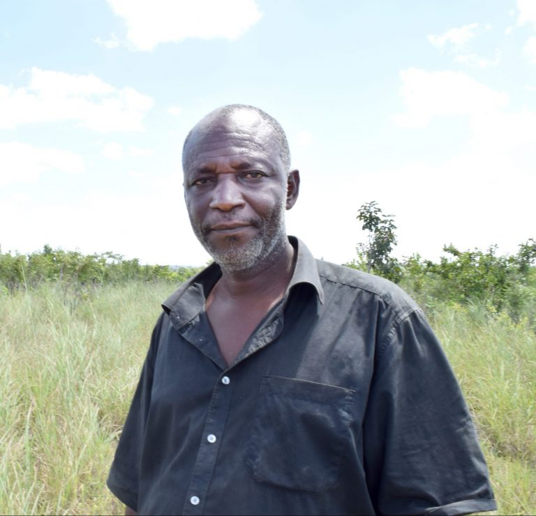 Mussa Said tittar in i kameran. Bakom honom syns högt gräs och buskar.