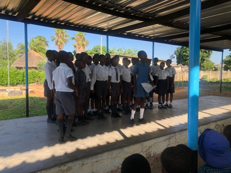 En skolklass som gått utbildningen står på ett podium utomhus och talar till en publik.