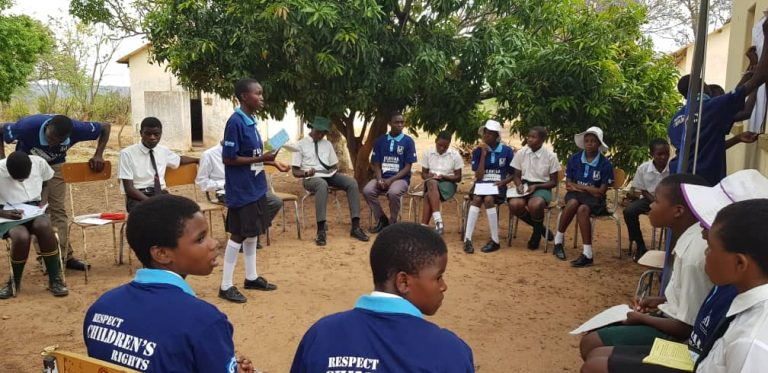 Elever från utbildningen och andra barn sitter i en ring i en trädgård. En av eleverna från utbildningen står i ringen och pratar medan en annan antecknar.
