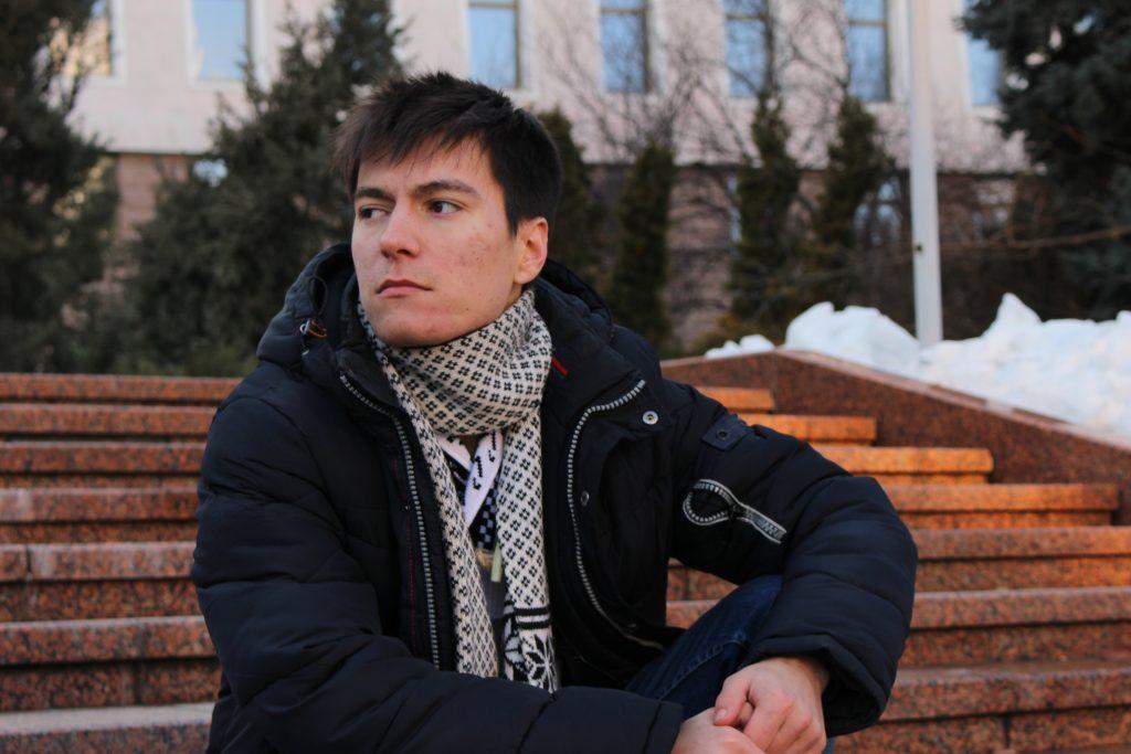 Andrei sitter på en trappa och tittar bort från kameran. Bakom honom syns en byggnad, snö och träd.