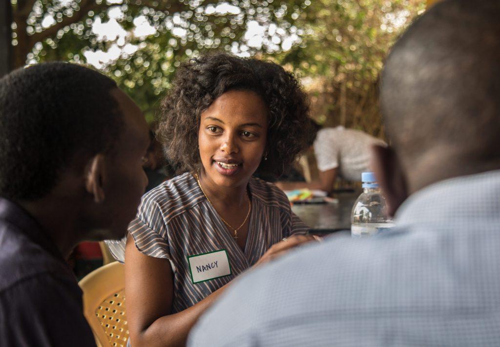 En kvinna med namnskylten Nancy sitter vid ett bord och pratar med två män.