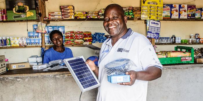 En man står i en butik och håller i solceller.