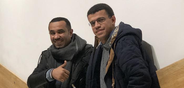 Två män står bredvid varandra. De har jackor och ler in i kamerna.