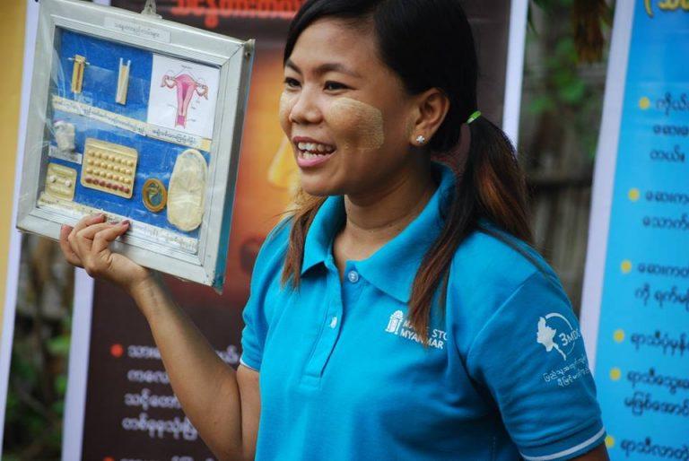 En kvinna med turkos tröja håller upp en skylt som visar olika preventivmedel.