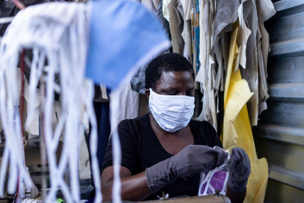 En kvinna med munskydd sitter och tillverkar munskydd i tyg.