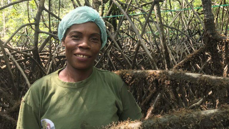 En kvinna, Merling, står i mangroveträsket och tittar leende rakt fram. Hon har en blå plastmössa på huvudet.