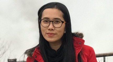 Ly Voucheng, en kvinna med röd jacka och långt hår står framför ett staket och tittar in i kameran.