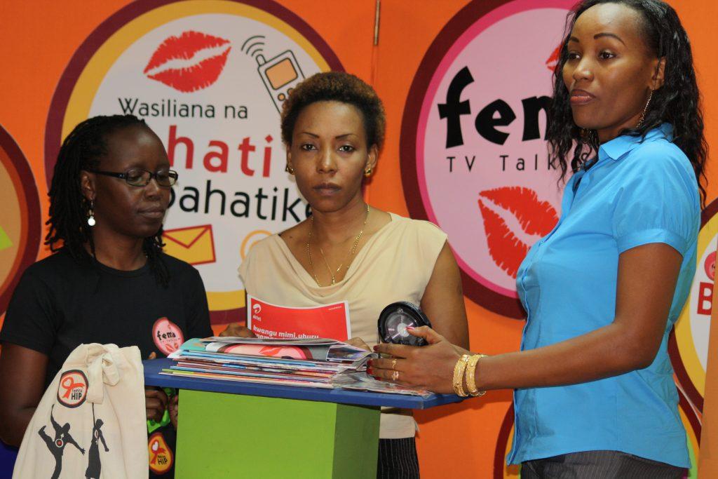 Tre kvinnor från organisationen femina Hip vid ett podium