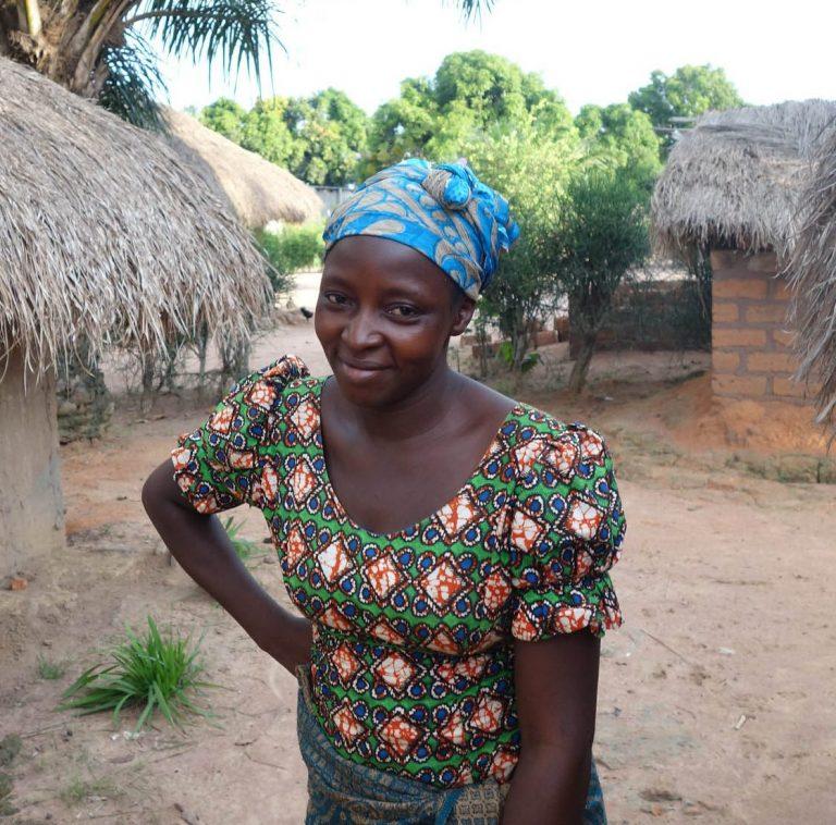 Kayalumbu Bembelesa står mellan två enkla hus och ler.
