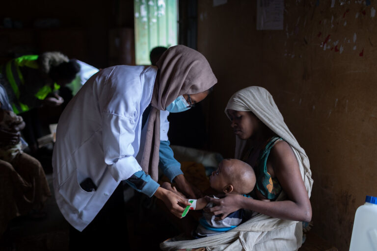 Sjukvårdspersonal mäter barnens överarmar