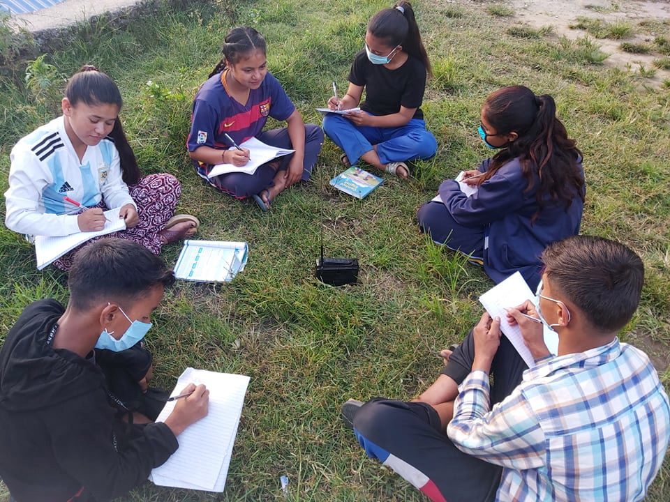 Sex ungdomar sitter på gräset runt en radio