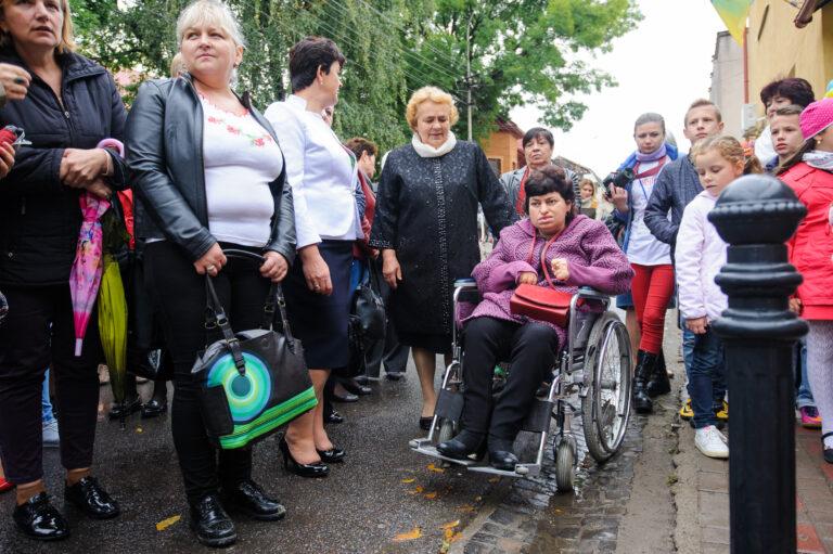En kvinna i rullstol omgiven av en massa människor på en gata.