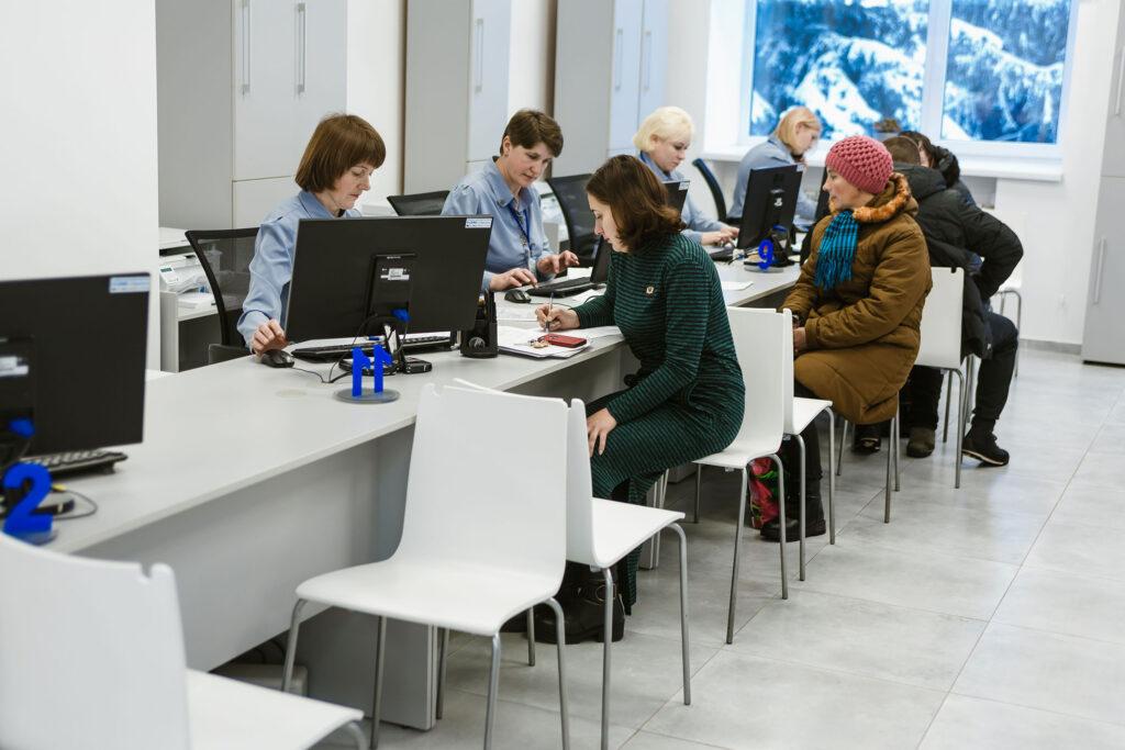 Besökare sitter vid en lång disk mitt emot medarbetare vid datorer